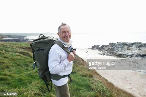 happy senior hiker with backpack on coastline. - 65 69 ans photos et images de collection