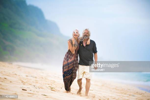 happy senior hippie couple strolling side by side on the beach - hippie stock pictures, royalty-free photos & images