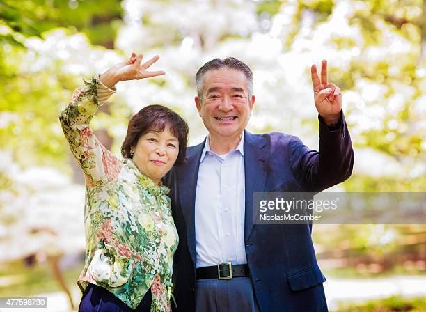 幸せなシニア日本のカップルのポートレート、楽しい peace サインが特長