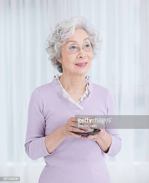 happy senior japanese woman with a cup of tea