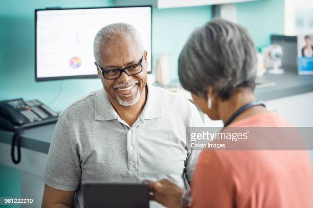 happy senior male patient talking to female doctor in clinic - cavan images foto e immagini stock