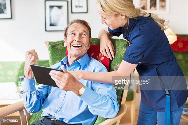 Happy senior man and female caretaker using digital tablet at nursing home