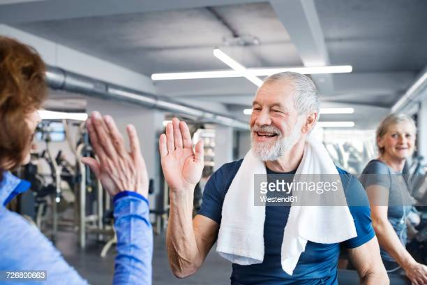 happy senior man and woman high fiving after working out in gym - fair play sport foto e immagini stock