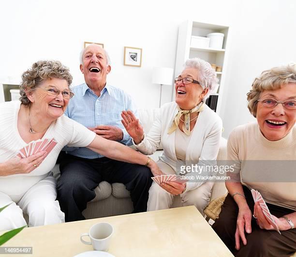 Happy senior Damen und Herren Spielkarten zu Hause fühlen