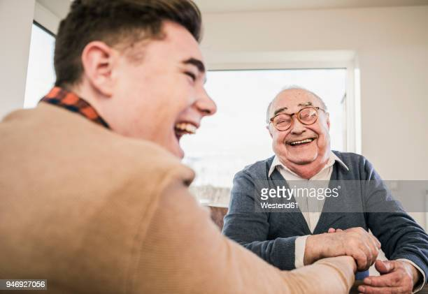 Happy senior man and young man arm wrestling