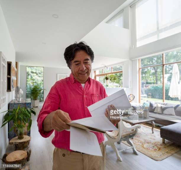 homem sênior feliz em casa que vai sobre seu sorriso do correio - responder - fotografias e filmes do acervo
