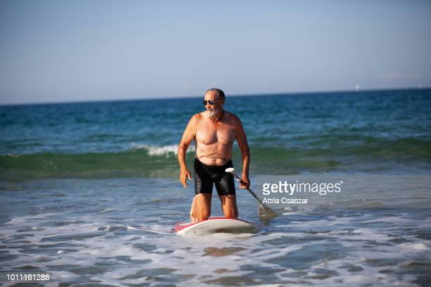Happy senior man coming out from ocean after paddle boarding