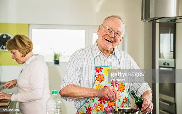 Happy senior man cooking in kitchen