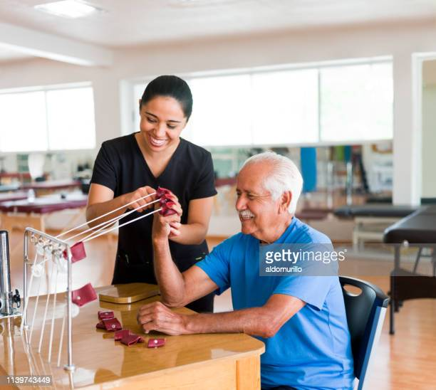 happy senior man exercising hand with physical therapy device - mid adult women stock pictures, royalty-free photos & images