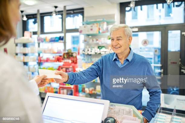 Happy senior man giving prescription to pharmacist