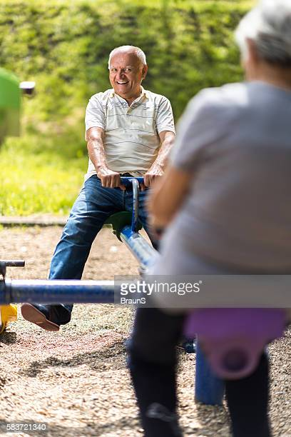 Happy senior man having fun on a seesaw.