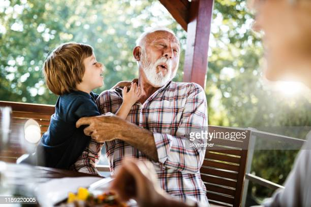 happy senior man having fun with his small grandson during a meal on a balcony. - grandson stock pictures, royalty-free photos & images