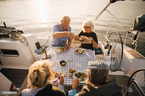happy senior man having sliced bread with friends in boat on sunny day - sailing stock pictures, royalty-free photos & images