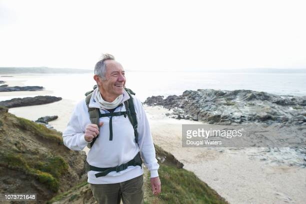happy senior man hiking along coastline. - dougal waters stock pictures, royalty-free photos & images
