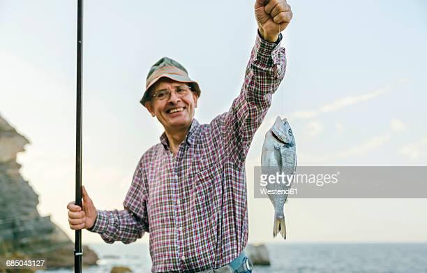 Happy senior man holding fish on fishing line
