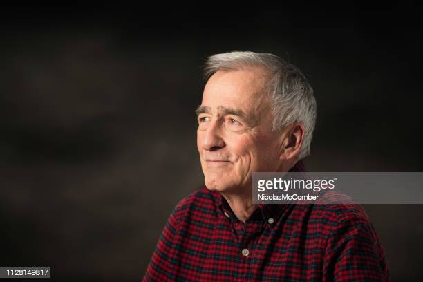 happy senior man in his late 70s studio portrait looking left with dark background - three quarter front view stock pictures, royalty-free photos & images