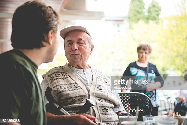 Happy Senior Man in Wheelchair and Grandson Having Coffee, Europe