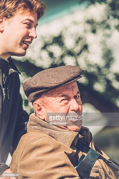 happy Senior Man in Wheelchair and Grandson Outdoors, Europe