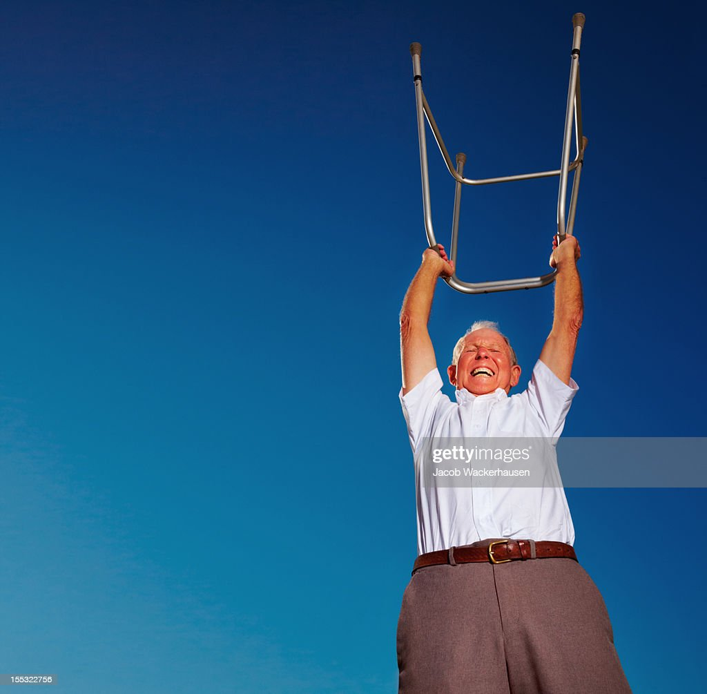 Happy senior man lifting a zimmer frame : Stock Photo