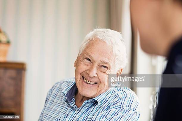Happy senior man looking at caretaker in nursing home