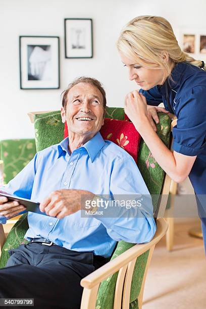 Happy senior man looking female caretaker while using digital tablet in nursing home