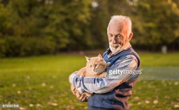 Happy senior man loves taking his male Maine Coon cat for a walk in the park.