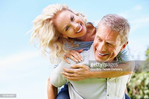 Happy senior man piggybacking mature woman