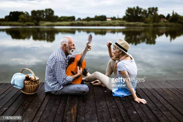 happy senior man playing a guitar to his wife on a pier in nature. - young at heart stock pictures, royalty-free photos & images