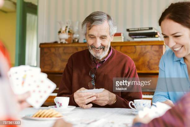 Happy senior man playing cards with family at home