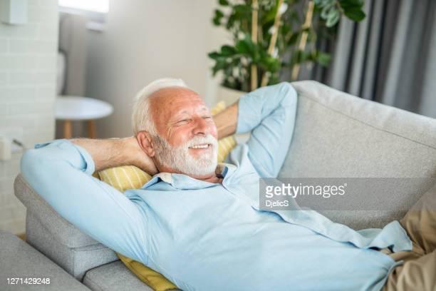 glücklicher senior mann entspannend auf dem sofa. - hände hinter dem kopf stock-fotos und bilder