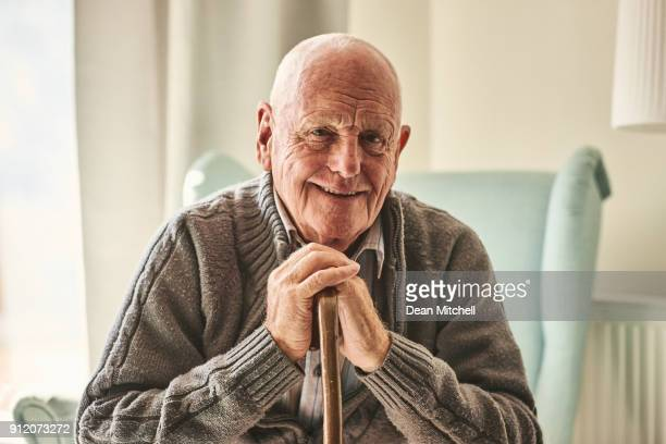 happy senior man sitting at home - senior adult stock pictures, royalty-free photos & images