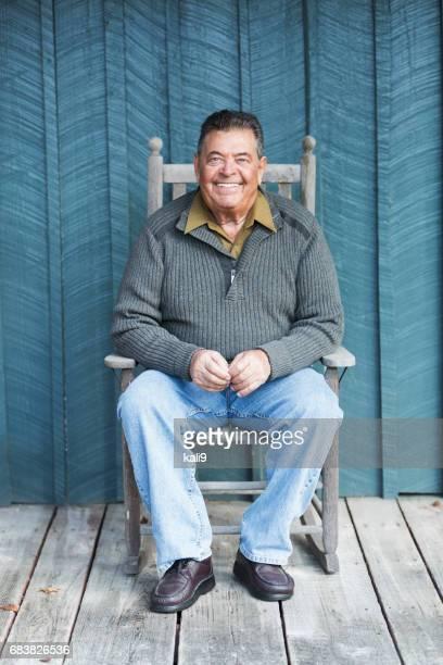 Glücklich senior Mann sitzt im Schaukelstuhl auf der Veranda