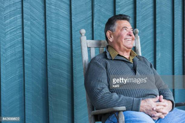 happy senior man sitting in rocking chair on porch - rocking chair stock photos and pictures
