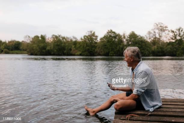 happy senior man sitting on jetty at a lake with cell phone - einzelner senior stock-fotos und bilder