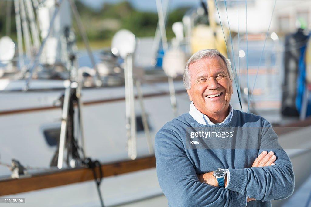 Happy senior man smiling on boat at harbor : Stockfoto