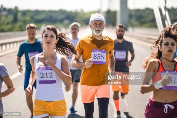 幸せな年配の男性は、道路上のマラソン大会に参加します。 - ハーフマラソン ストックフォトと画像