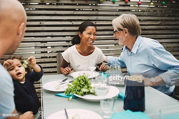 Happy senior man talking to daughter-in-law at outdoor dining table