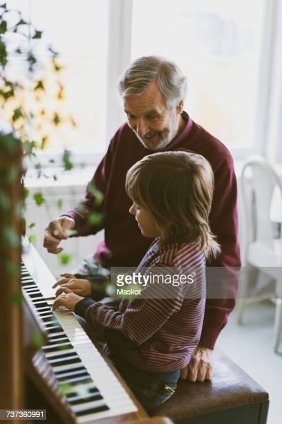 happy senior man talking to great grandfather playing piano at home - klaverin och tangentinstrument bildbanksfoton och bilder