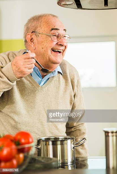 Happy senior man tasting from cooking pot in kitchen