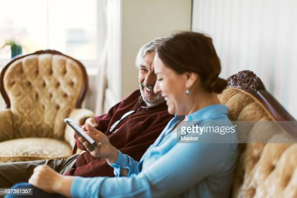Happy senior man using smart phone with daughter in living room