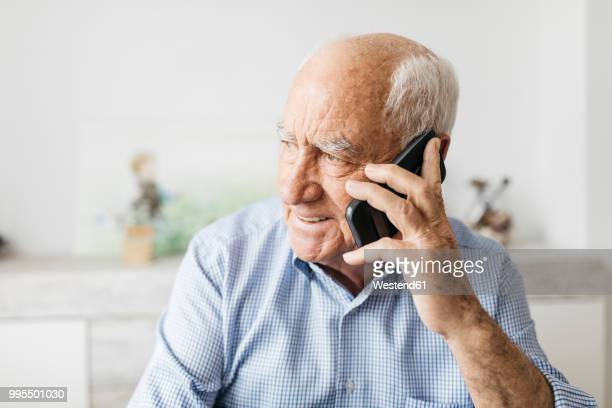 happy senior man using smartphone at home - telefoon gebruiken stockfoto's en -beelden