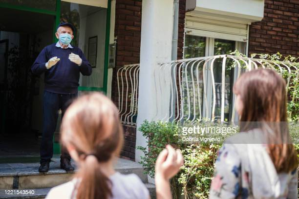 happy senior man wearing protective mask and gloves while waiting for his granddaughters outdoors - visit stock pictures, royalty-free photos & images