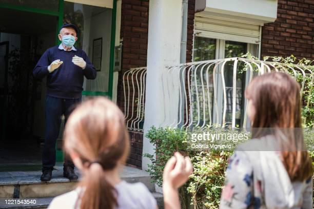 gelukkige hogere mens die beschermend masker en handschoenen draagt terwijl het wachten op zijn kleindochters in openlucht - bezoek stockfoto's en -beelden