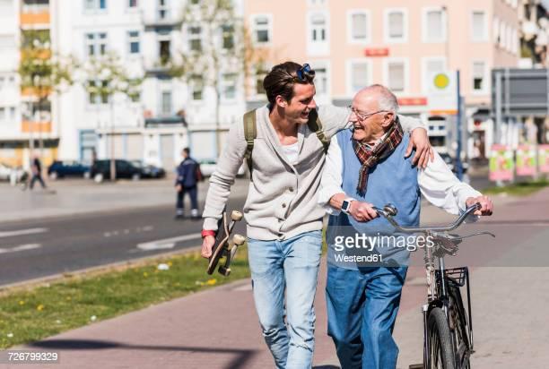 happy senior man with adult grandson in the city on the move - jung geblieben stock-fotos und bilder