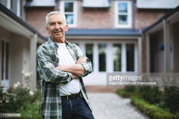 Happy senior man with arms crossed against house