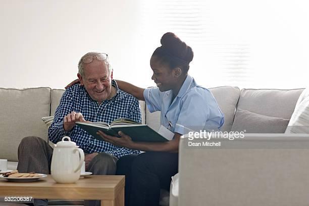 Happy senior man with carer reading a novel together