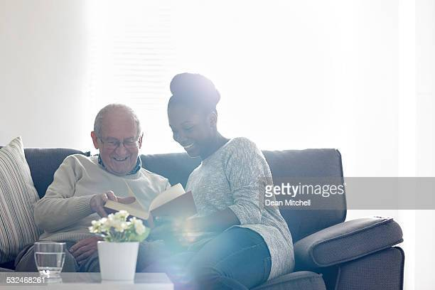 Happy senior man with female carer reading a book