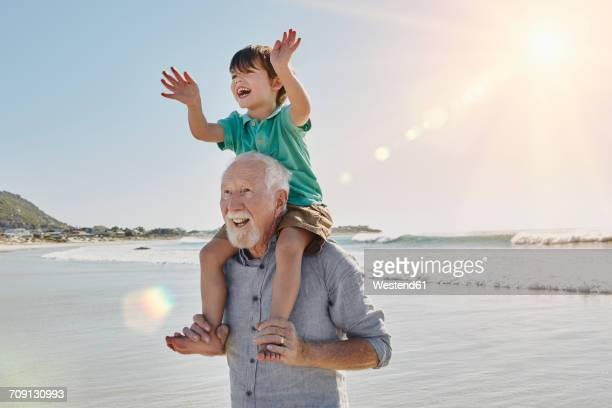 Happy senior man with grandson on his shoulders on the beach