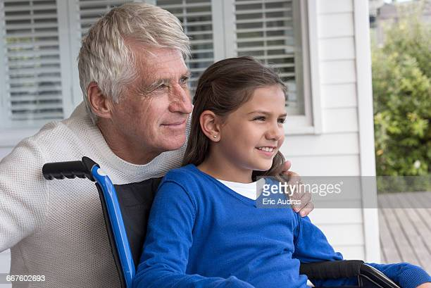 Happy senior man with his granddaughter in wheelchair on porch
