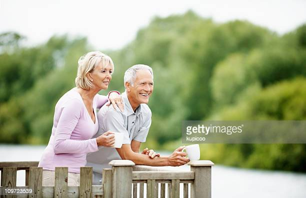 Happy senior man with mature woman holding cup of tea